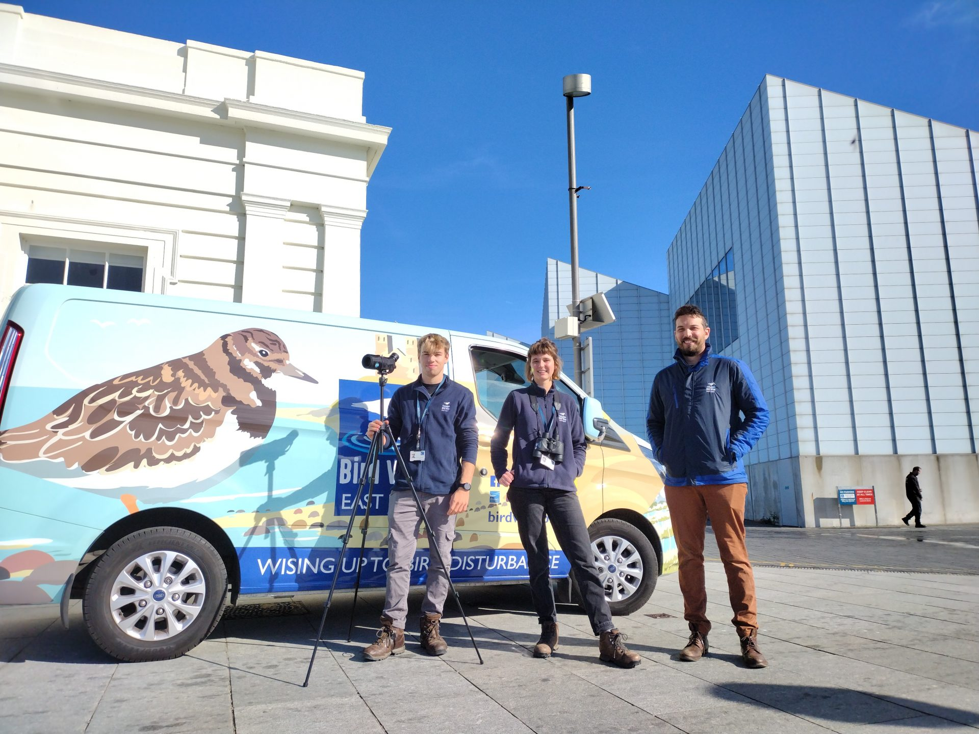 Colourful birdwise transit van sits in front of bright blue sky. Three people standing in front smiling.