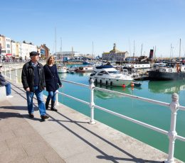 Two people walking on the left hand side adjacent to railings and blue sea. Moored boats and buildings in the background of the photo.